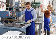 Купить «Male glazier working with glass on drilling machine», фото № 30387798, снято 10 сентября 2018 г. (c) Яков Филимонов / Фотобанк Лори