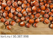 Unpeeled hazelnut on natural wooden background, nobody. Стоковое фото, фотограф Яков Филимонов / Фотобанк Лори