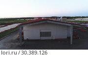 Купить «The territory of an industrial plant. Large hangars with a red roof. Aerial view, evening shooting», видеоролик № 30389126, снято 4 июля 2018 г. (c) Андрей Радченко / Фотобанк Лори