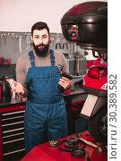 Купить «Worker inspects a motorcycle», фото № 30389582, снято 20 июня 2019 г. (c) Яков Филимонов / Фотобанк Лори