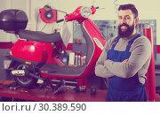 Купить «positive man worker displaying his workplace in motorcycle workshop», фото № 30389590, снято 19 апреля 2019 г. (c) Яков Филимонов / Фотобанк Лори