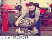 Купить «Man 20-30years old is working at restoring wheel», фото № 30389594, снято 20 июня 2019 г. (c) Яков Филимонов / Фотобанк Лори