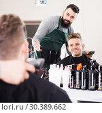 Купить «Hairdresser displaying result of work», фото № 30389662, снято 27 января 2017 г. (c) Яков Филимонов / Фотобанк Лори
