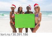 Купить «Multi-ethnic female friends holding a empty green placard at beach on a sunny day», фото № 30391186, снято 12 ноября 2018 г. (c) Wavebreak Media / Фотобанк Лори