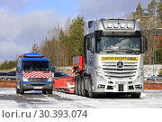 Купить «Salo, Finland - March 9, 2019: Silver Mercedes-Benz Actros 4163 truck and trailer for heavy duty oversize load transport with pilot vehicle parked.», фото № 30393074, снято 9 марта 2019 г. (c) age Fotostock / Фотобанк Лори