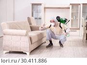 Купить «Pest control contractor working in the flat», фото № 30411886, снято 12 ноября 2018 г. (c) Elnur / Фотобанк Лори
