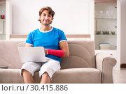 Купить «Young man with injured arm sitting on the sofa», фото № 30415886, снято 19 сентября 2018 г. (c) Elnur / Фотобанк Лори