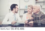 Купить «Woman and eldery man with bank employee», фото № 30416486, снято 27 мая 2020 г. (c) Яков Филимонов / Фотобанк Лори