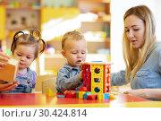 Kindergarten teacher playing with babies in nursery. Developmental toys for preschool. Стоковое фото, фотограф Оксана Кузьмина / Фотобанк Лори
