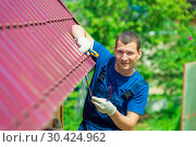Купить «A young man repairs the roof of the house in overalls with a tool», фото № 30424962, снято 23 июня 2016 г. (c) Константин Лабунский / Фотобанк Лори