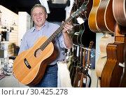 Купить «Man musician holding new wooden acoustic guitar», фото № 30425278, снято 18 сентября 2017 г. (c) Яков Филимонов / Фотобанк Лори