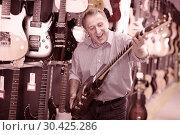 Купить «male demonstrating an electric guitar», фото № 30425286, снято 18 сентября 2017 г. (c) Яков Филимонов / Фотобанк Лори