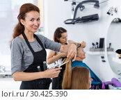 Купить «Hairdresser doing styling of girl», фото № 30425390, снято 26 июня 2018 г. (c) Яков Филимонов / Фотобанк Лори