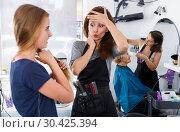 Купить «Puzzled hairstylist inspecting hair of teen girl», фото № 30425394, снято 26 июня 2018 г. (c) Яков Филимонов / Фотобанк Лори