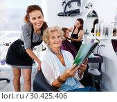 Купить «Young woman hairdresser in hair salon helping to senior woman choosing hairstyling», фото № 30425406, снято 26 июня 2018 г. (c) Яков Филимонов / Фотобанк Лори