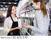 Купить «Young woman hairdresser helping woman client with choice of shampoo in shop», фото № 30425570, снято 31 марта 2018 г. (c) Яков Филимонов / Фотобанк Лори