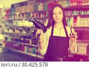 Купить «Woman hairstylist holding blow dryer and hair cutters in cosmetics salon», фото № 30425578, снято 31 марта 2018 г. (c) Яков Филимонов / Фотобанк Лори