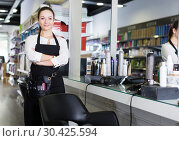 Купить «Young worker female hairstylist standing in cosmetics studio», фото № 30425594, снято 31 марта 2018 г. (c) Яков Филимонов / Фотобанк Лори