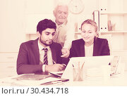 Купить «Office workers are demonstrating reports on laptop to mature boss», фото № 30434718, снято 27 июня 2017 г. (c) Яков Филимонов / Фотобанк Лори