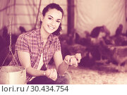 Купить «Portrait of young woman farmer holding fresh eggs in hands in henhouse», фото № 30434754, снято 23 апреля 2019 г. (c) Яков Филимонов / Фотобанк Лори