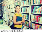 Купить «Young glad woman shopping books in bookstore», фото № 30434862, снято 23 мая 2019 г. (c) Яков Филимонов / Фотобанк Лори