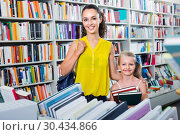 Купить «Glad woman with girl taking literature books», фото № 30434866, снято 8 декабря 2019 г. (c) Яков Филимонов / Фотобанк Лори