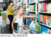 Купить «Woman with girl buying books», фото № 30434870, снято 25 апреля 2019 г. (c) Яков Филимонов / Фотобанк Лори