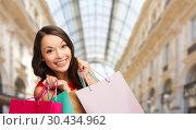 Купить «woman with shopping bags over mall background», фото № 30434962, снято 22 сентября 2013 г. (c) Syda Productions / Фотобанк Лори