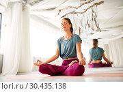 Купить «woman meditating in lotus pose at yoga studio», фото № 30435138, снято 21 июня 2018 г. (c) Syda Productions / Фотобанк Лори