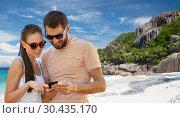 Купить «happy couple with smartphone on seychelles island», фото № 30435170, снято 15 июля 2018 г. (c) Syda Productions / Фотобанк Лори