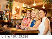 Купить «women taking picture by selfie stick at wine bar», фото № 30435326, снято 25 июня 2018 г. (c) Syda Productions / Фотобанк Лори