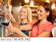 Купить «happy women pouring wine from dispenser at bar», фото № 30435342, снято 25 июня 2018 г. (c) Syda Productions / Фотобанк Лори