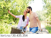 couple with bicycles taking selfie by smartphone. Стоковое фото, фотограф Syda Productions / Фотобанк Лори