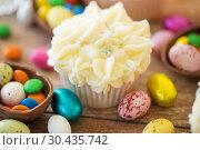 Купить «cupcake with chocolate eggs and candies on table», фото № 30435742, снято 15 марта 2018 г. (c) Syda Productions / Фотобанк Лори