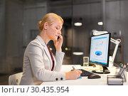 Купить «businesswoman calling on sartphone at night office», фото № 30435954, снято 6 декабря 2017 г. (c) Syda Productions / Фотобанк Лори
