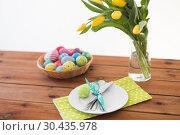 Купить «easter eggs in basket, plates, cutlery and flowers», фото № 30435978, снято 15 марта 2018 г. (c) Syda Productions / Фотобанк Лори