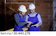 Купить «Portrait of two builders reading plan of brick building», видеоролик № 30443278, снято 22 февраля 2019 г. (c) Яков Филимонов / Фотобанк Лори