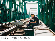 Купить «Young construction worker man rests sitting reading a book on an old steel railway bridge.», фото № 30446946, снято 27 марта 2019 г. (c) easy Fotostock / Фотобанк Лори