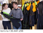 Купить «Girl seller is helping man choose new costume for diving», фото № 30447298, снято 25 января 2018 г. (c) Яков Филимонов / Фотобанк Лори