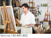 Купить «Man near easel painting on canvas», фото № 30447402, снято 8 апреля 2017 г. (c) Яков Филимонов / Фотобанк Лори
