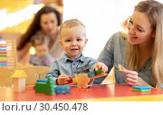 Kindergarten teacher playing with kid in nursery. Developmental toys for preschool. Стоковое фото, фотограф Оксана Кузьмина / Фотобанк Лори