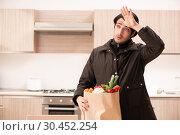 Купить «Young handsome man with vegetables in the kitchen», фото № 30452254, снято 28 ноября 2018 г. (c) Elnur / Фотобанк Лори