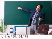 Купить «Male teacher drinking in the classroom», фото № 30454178, снято 21 декабря 2018 г. (c) Elnur / Фотобанк Лори
