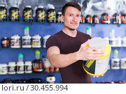 Купить «Young muscular guy looking sport nutrition products in store», фото № 30455994, снято 12 апреля 2018 г. (c) Яков Филимонов / Фотобанк Лори