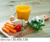 Купить «Freshly squeezed carrot-ginger juice», фото № 30456138, снято 20 мая 2019 г. (c) Яков Филимонов / Фотобанк Лори