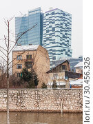 View of modern glass buildings and old brick houses. New skyscrapers growing over the old buildings in Sarajevo (2018 год). Редакционное фото, фотограф Николай Коржов / Фотобанк Лори