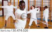 Купить «African American fencer practicing effective fencing techniques in training room», фото № 30474026, снято 30 мая 2018 г. (c) Яков Филимонов / Фотобанк Лори