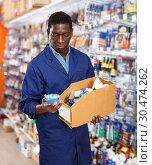 Купить «seller organizing assortment of items on shelves and racks», фото № 30474262, снято 21 января 2019 г. (c) Яков Филимонов / Фотобанк Лори
