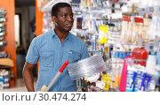 Купить «seller organizing assortment of items on shelves and racks», фото № 30474274, снято 21 января 2019 г. (c) Яков Филимонов / Фотобанк Лори
