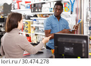 Купить «Ordinary salesman offering tools to young woman», фото № 30474278, снято 21 января 2019 г. (c) Яков Филимонов / Фотобанк Лори